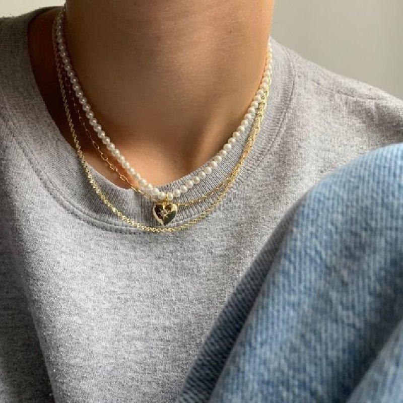 Photo du cou d'une personne. Elle porte un collier de perles avec un pendentif en forme de cœur, une chaîne en or et une blouse grise.
