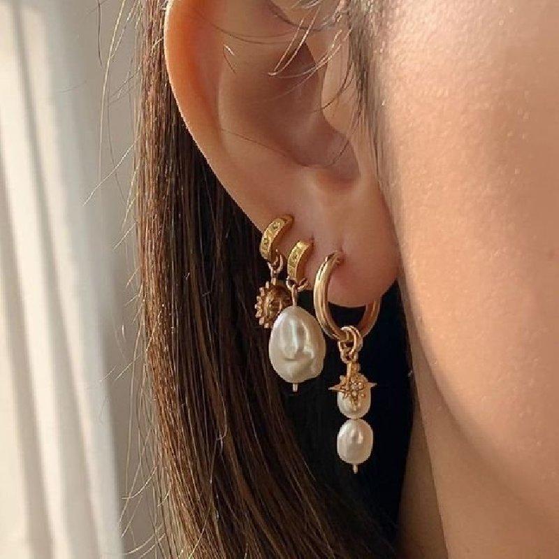 Photo d'une oreille de femme avec trois boucles d'oreille en or, deux d'entre elles ont un pendentif en perle.