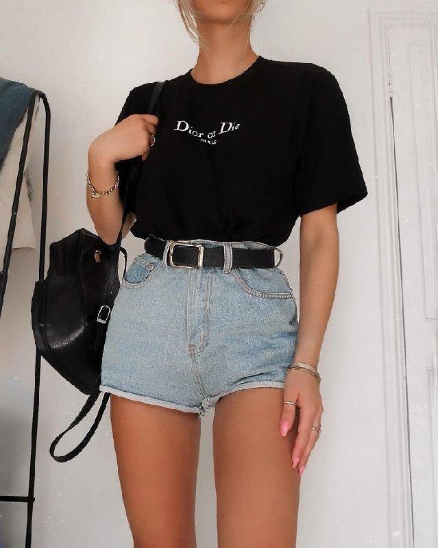 Photo du look d'une femme. Elle porte un t-shirt noir, un short en jean avec une ceinture noire et un sac à dos noir.