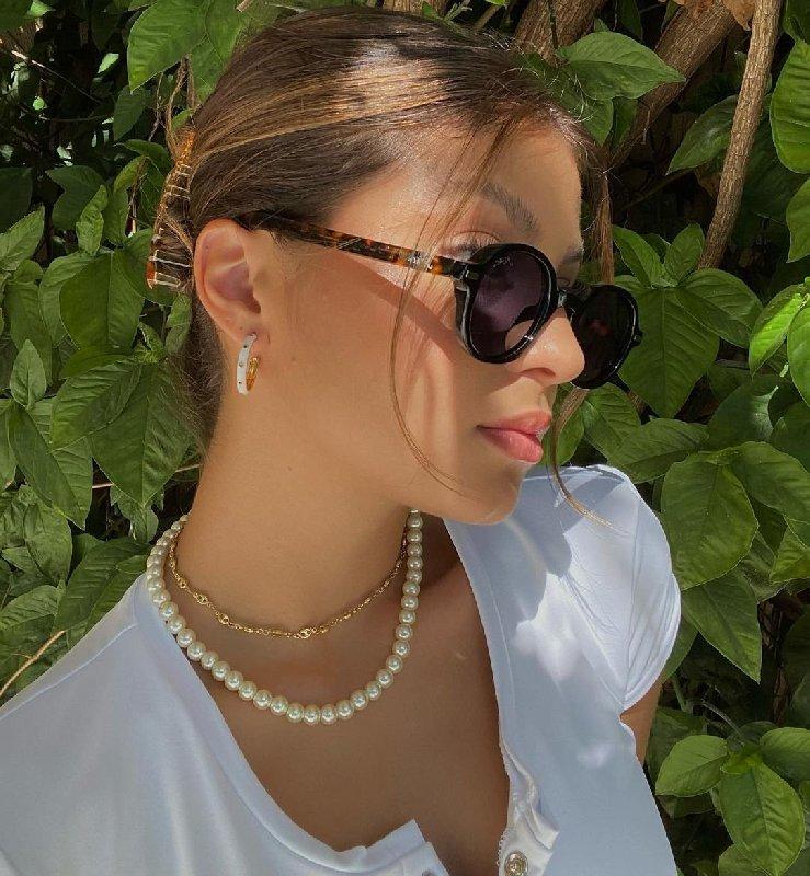 Selfie d'une fille avec des lunettes de soleil brunes de profil. Elle porte un chemisier blanc, des colliers, des boucles d'oreilles en forme de cerceau et des cheveux attachés en chignon.